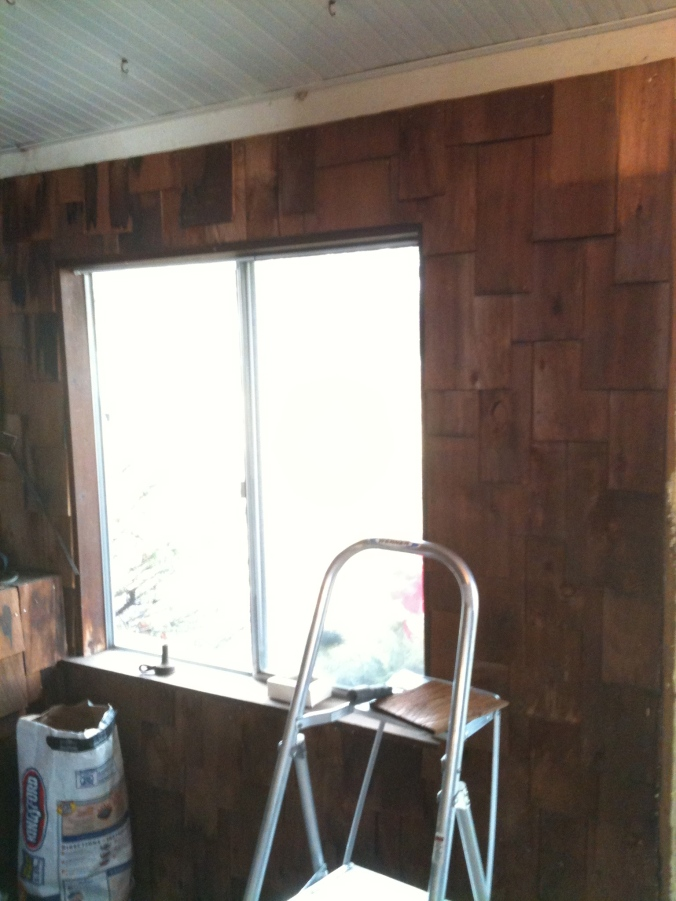 One of the mudroom walls covered in cedar shakes