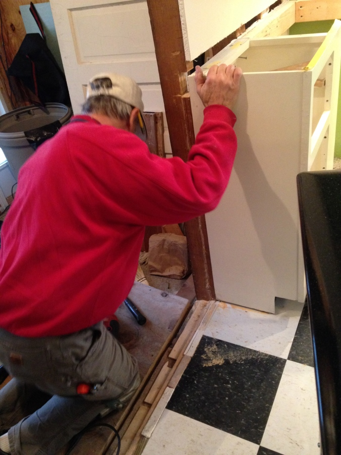 The dry wall was cut out, and the stud at the corner was notched to enable the cabinet to slide back 5/8 of an inch.