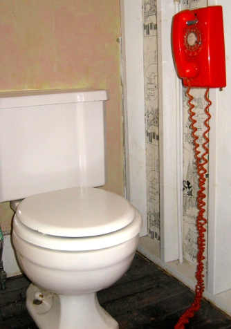 Orange phone hanging by the toilet