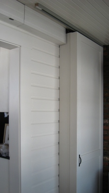 And the pocket door painted and closed. Here at the top, you can see the secret hinged cover that opens to allow access to the wires.